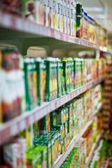 Shelves with juices in a supermarket. Blur