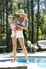 Mother carrying six month old baby next to a swimming pool