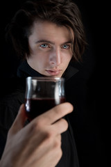 Handsome vampire with pale skin and blue eyes holding glass of w