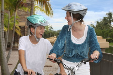 Mother and son biking together in the city with laughter