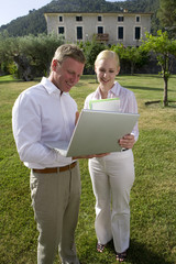 Businessman and businesswoman using laptop in grass behind manor