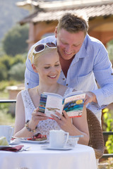 Couple looking at travel guidebook on cafe patio