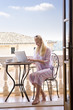 Woman in pajamas using laptop on balcony