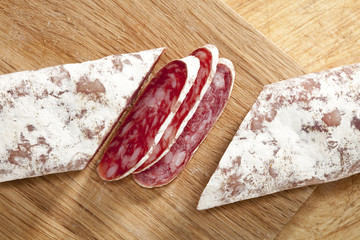spanish fuet salami cuts on wooden board