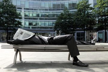 young caucasian businessman lying on bench with newspapper on hi