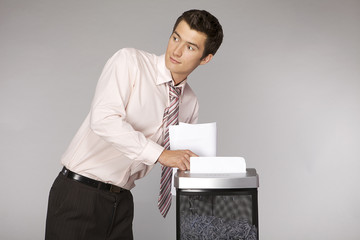 Young caucasian businessman shredding documents
