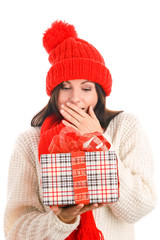 Surprised young woman holding gift covering her mouth