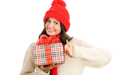 Pretty young woman holding gift giving thumbs up