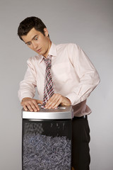 Young caucasian businessman with tie trapped in shredded machine