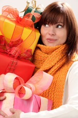 Portrait of young surprised woman holding gifts
