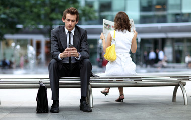 young caucasian businessman sitting on bench using his phone
