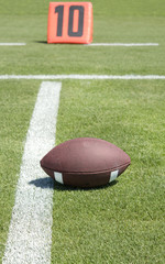 American football on ten yard line of field