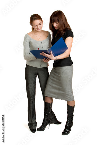Two young women get acquainted oneself with the document.