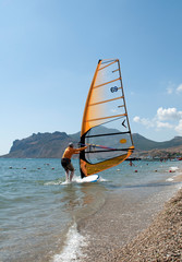 Windsurfer starting sailing on the waves