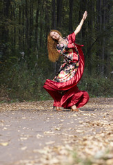 A beautiful ginger-haired girl in gipsy suit dancing in fall