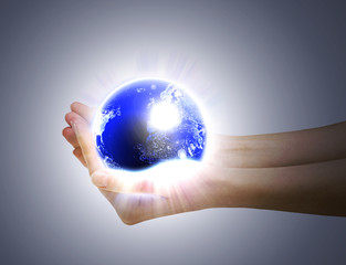 Human hands holding glowing planet