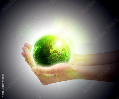 Ludzkie ręce trzyma świecącą zieloną planetę