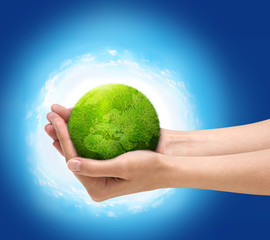 Human hands holding green planet