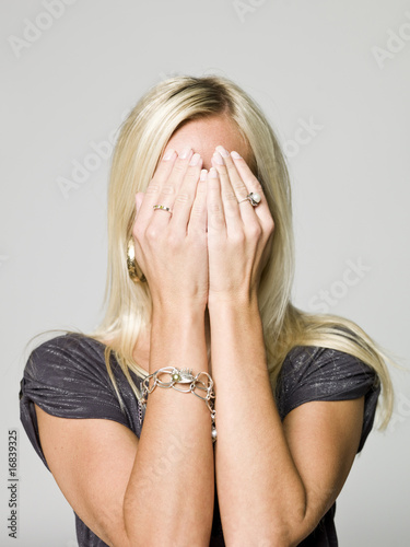 Portrait of a woman hiding in her hands