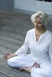Fototapety Seniorin macht Yoga auf der Terrasse