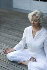 Seniorin macht Yoga auf der Terrasse