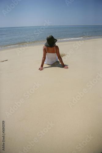 femme assise sur le sable au bord de la mer de auremar. Black Bedroom Furniture Sets. Home Design Ideas