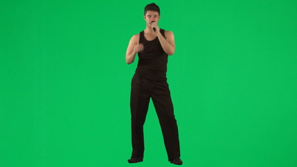 Man singing with a microphone against green screen