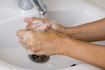 Young woman washing hands as prevention against grip