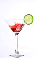 red cocktail with lime on white