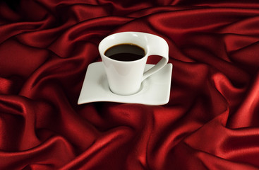 Cup of coffee on red satin