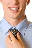 Photo of happy smiling businessman fastening tie, isolated poster