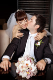 Groom kissing bride in the cheek with wedding bouquet poster