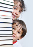 Fototapety A big tower of many books vertical and kids hiding behind