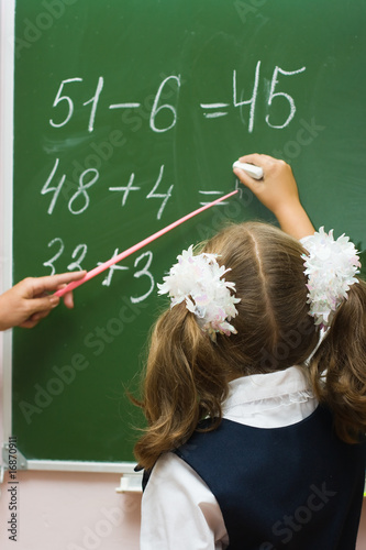The schoolgirl at a school board at a mathematics lesson.