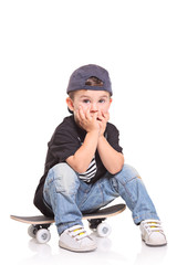 Little child sitting on a skateboard isolated on white