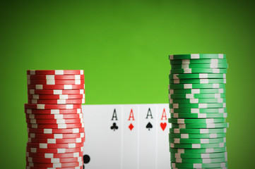 Casino chips and four aces against green background