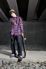 Skateboarder standing on path underground
