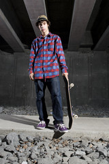 Skateboarder standing on path holding board