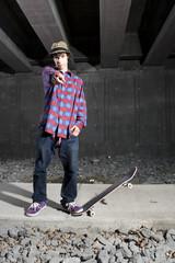 Skateboarder standing on footpath