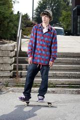 Fashionable skateboarder standing on board