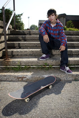 Young skateboarder sitting on stairs