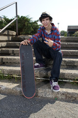 Skateboarder sitting on stairs