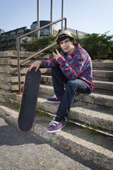 Teenage skateboarder sitting on stairs