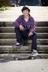 Skateboarder sitting down smiling for camera