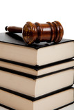Wooden gavel on top of a stack of law books poster