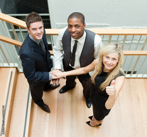 Businesspeople with hands together and looking at the camera