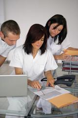 homme et femmes en blouse blanche lisant un document
