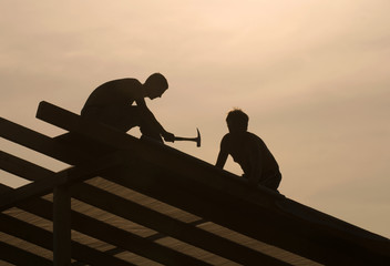Shot of a carpenter swinging his hammer constructing an roof.
