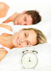 Couple in bed with alarm clock and woman smiling at the camera