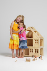 Young girls standing with dolls house